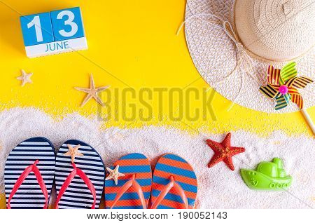 June 13th. Image of june 13 calendar on yellow sandy background with summer beach, traveler outfit and accessories. Summertime concept.