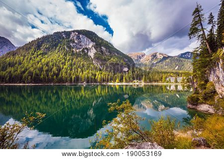 South Tyrol, Italy. Magnificent lake Lago di Braies. The concept of walking and eco-tourism. Emerald expanse of water reflects the surrounding forest and mountains