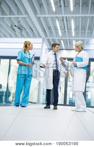 Medical team interacting with each other in corridor at hospital