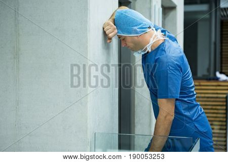 Tensed male surgeon leaning on wall near elevator in hospital