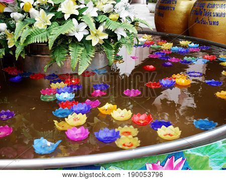 Ritual praying colorful candle floating on water for pray buddha at Wat Phra Pathommachedi Ratcha Wora Maha Wihan in Nakhon Pathom, Thailand