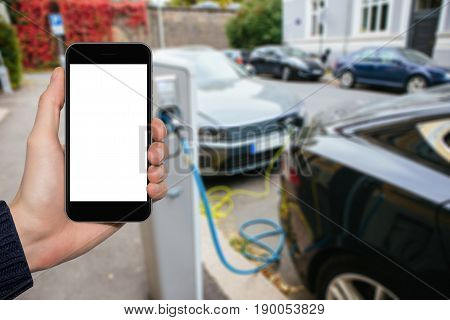 Hand with phone on a background of electric cars charging points. White screen, you can insert your own image or text here.