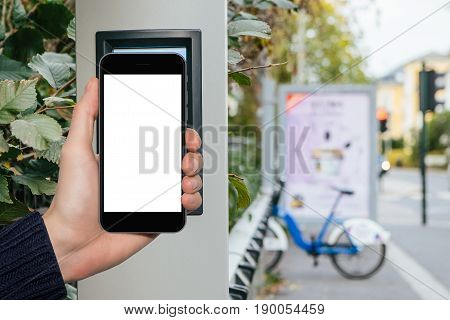 Hand with phone on a background of bicycle rental. White screen, you can insert your own image or text here.