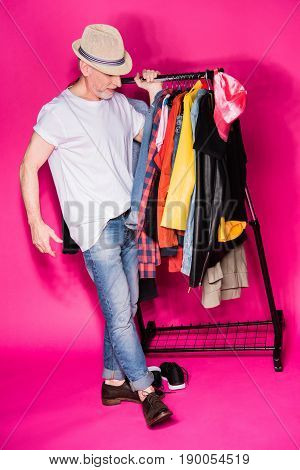 Stylish Senior Man Wearing Hat And Carrying Diferent Clothes On Hangers Isolated On Pink