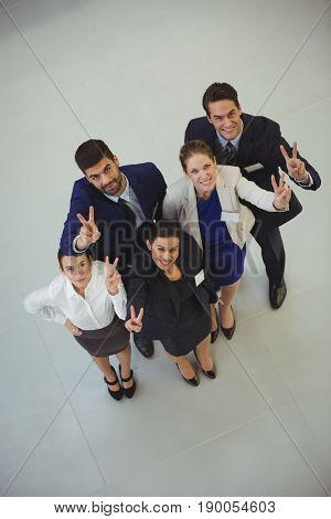 Successful businesspeople showing victory sign in office
