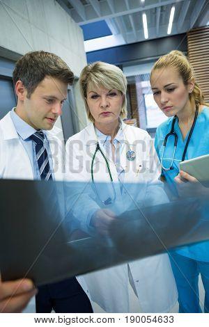 Medical team examining x-ray report in corridor at hospital
