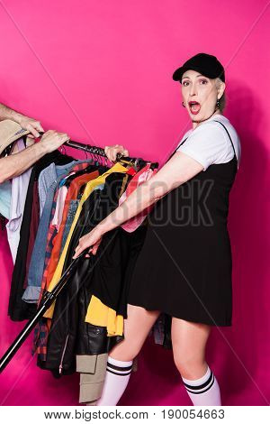 Shocked Senior Woman Holding Wardrobe With Diferent Clothes On Hangers Isolated On Pink