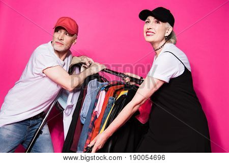 Smiling Stylish Senior Couple Holding Wardrobe With Diferent Clothes On Hangers Isolated On Pink
