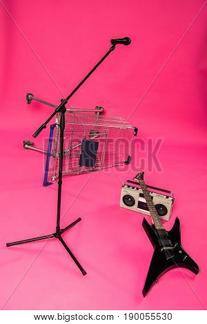 Electric Guitar With Tape Recorder, Microphone And Shopping Trolley Isolated On Pink
