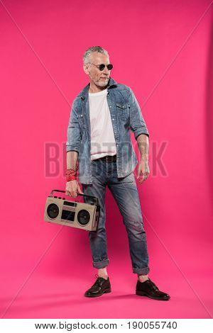stylish confident man holding tape recorder in hand and looking away isolated on pink