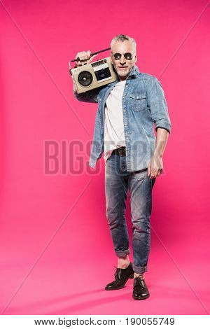 senior stylish man holding tape recorder on shoulder and looking at camera isolated on pink
