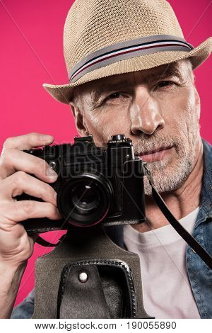 Portrait Of Confident Photographer Holding Photo Camera And Looking At Camera Isolated On Pink