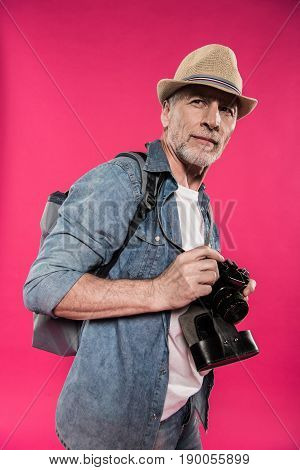 Portrait Of Confident Man In Hat Holding Photo Camera And Looking Away Isolated On Pink