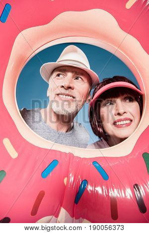 portrait of carefree elderly couple smiling into swimming tube
