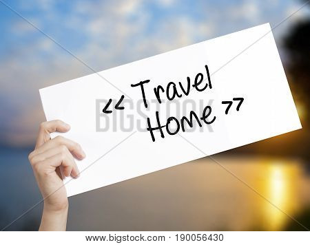 Travel - Home Sign On White Paper. Man Hand Holding Paper With Text. Isolated On Sunset Background