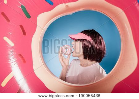 Stylish Woman Eating Sweet Doughnut Into Swimming Tube