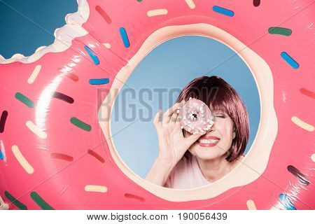 Smiling Woman Holding Doughnut In Front Of Eye Into Swimming Tube