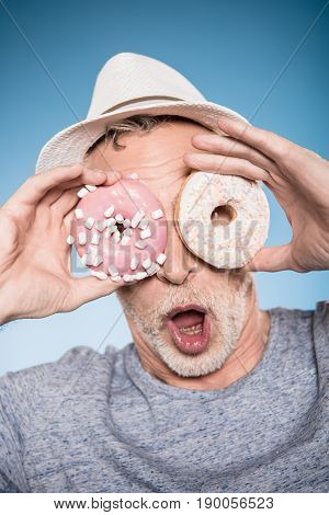 portrait of elderly casual man holding donuts in front of eyes