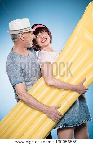 Sweetheart Casual Elderly Couple Holding Swimming Mattress
