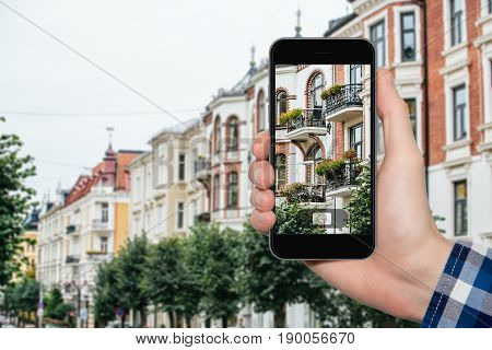 Hand with phone on a background of a city.