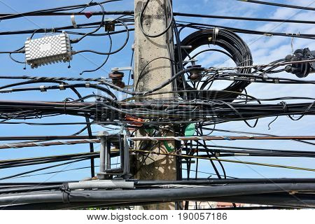A tangle of electric pole cables and wires and telephon in Thailand Asia