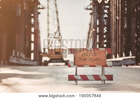 View on unfinished construction on the street. Warning about the end of the road.
