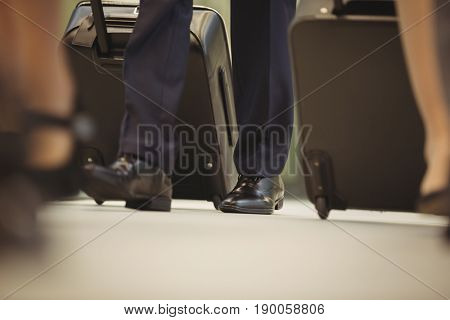 Low section of businessman with trolley bag walking