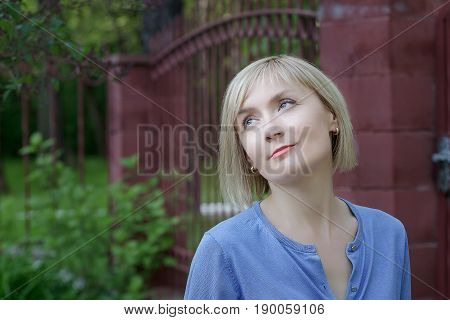 Outdoors portrait of mature woman at concrete fence with marsala color gates background