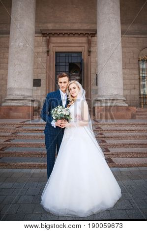 Wedding couple near a church. Wedding couple is hugging each other. Beauty bride with groom . Beautiful model girl in white dress. Man in suit.