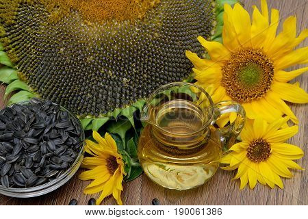 Oil seeds and sunflowers on a wooden background. Horizontal photo.