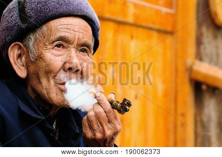 ZHAOXING CHINA - 11 NOVEMBER 2010: Old Chinese resting on the doorstep of his cottage smoking a pipe in the village Zhaoxing