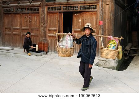 ZHAOXING CHINA - 12 NOVEMBER 2010: Residents of the Zhaoxing is a pretty Dong minority town carrying things on the stick for the sale