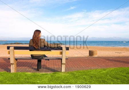 Beautiful Brunette Sitting On Bench At Sea