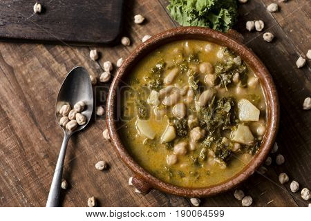closeup of an earthenware bowl with kale stew with potatoes and chickpeas, on a rustic wooden table sprinkled with some dry chickpeas