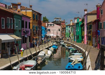 BURANO, ITALY - MAY 23, 2017: Canal with boats in the center of Burano island
