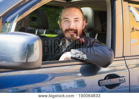 Smiling Asian Man Smoking Pipe. Driver