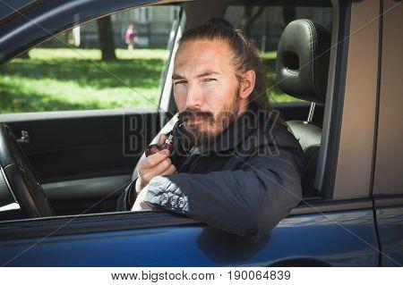 Serious Asian Man Smoking Pipe. Driver