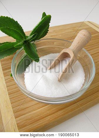 Stevia sugar free crystals in bowl an fresh stevia leaves