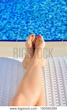 Woman Legs With Red Nails On A Lounger Near The Pool