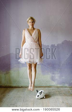 Cute blonde woman levitating by a white rabbit