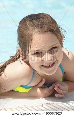 A happy little caucasian girl smiling on ledge pool of a camping resort in the summer sunny day.