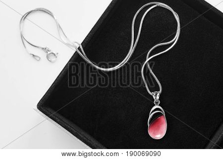 Pink coral pendant on silver chain in jewel box closeup
