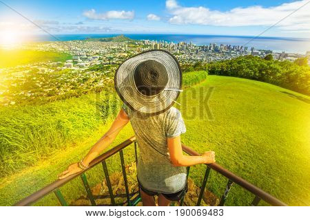 Tantalus Lookout at sunset, Puu Ualakaa State Park. Woman whit floppy hat looking Honolulu skyline, Waikiki Beach and Diamond Head. Waikiki cityscape, Oahu Hawaii, USA. Vacation and travel concept.