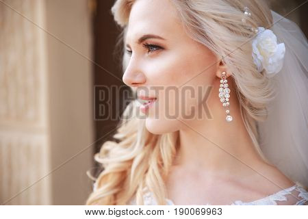 A beautiful bride looking to the side outdoors.Beautiful bride with bouquet of flowers outdoor . Beautiful bride posing in her wedding day