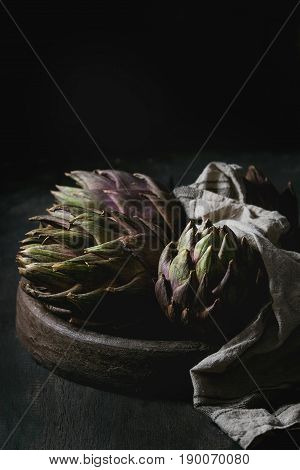 Uncooked whole organic wet purple artichokes in terracotta tray with textile over dark wooden background. Rustic style.
