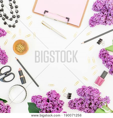 Blogger or freelancer round workspace with clipboard, cosmetics, branches of lilac and accessories on white background. Flat lay, top view. Beauty blogger concept.