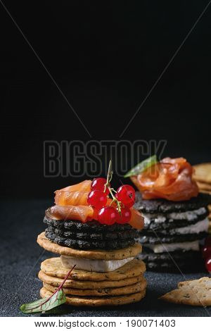 Stack of black wholegrain charcoal and traditional crackers with smoked salmon, cream cheese, green salad and red currant berries over black stone background. Appetizer snack. Space for text. Close up