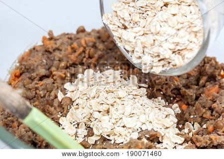 Lentil Burger Preparation : Adding oats to mashed lentils mix to prepare lentils burger