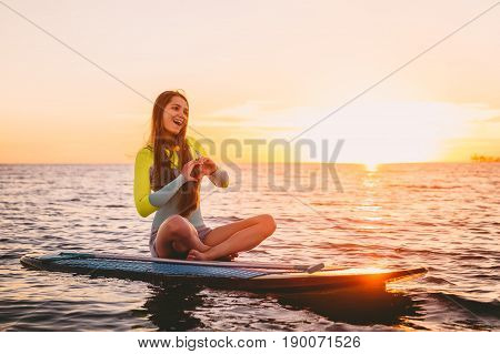 Stand up paddle boarding on a quiet sea with warm summer sunset colors. Happy smiling girl on board at sunset