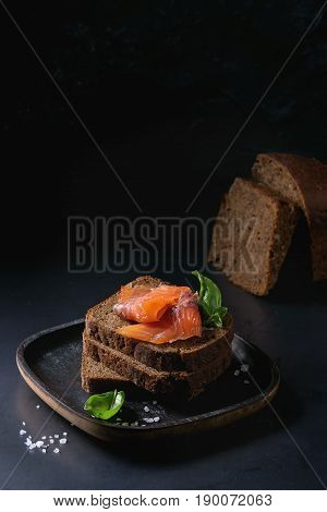 Stack of sliced homemade rye bread with smoked salmon, sea salt and fresh basil on wooden plate over dark black background.